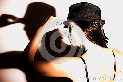 Dramatic profile portrait of a woman in a hat