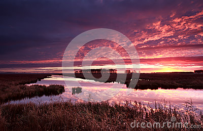 Dramatic red fire sunrise over river