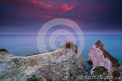Dramatic red sunrise over cliffs in ocean