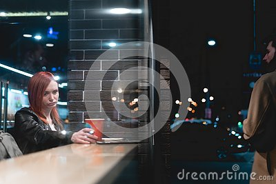 Dramatic scene, girl working on laptop in cafe, hold smartphone in hands, pen, use phone. Freelancer works remotely. Online, Stock Photo
