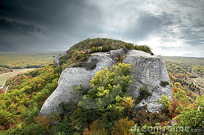 Dramatic scene of a rock with grey clouds