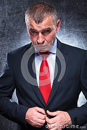Dramatic serious mature business man unbuttoning his coat