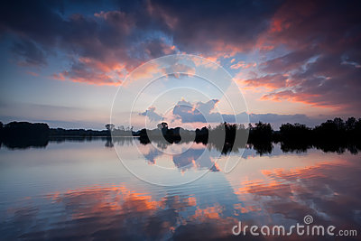 Dramatic sky reflected in lake at sunrise