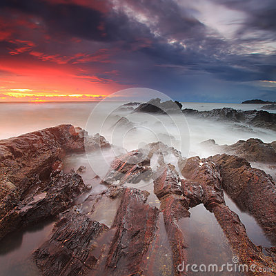Dramatic sunrise over rocky shoreline