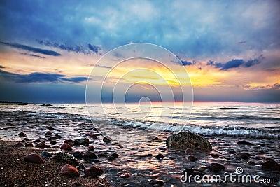 Dramatic sunrise on a rocky beach. Baltic sea
