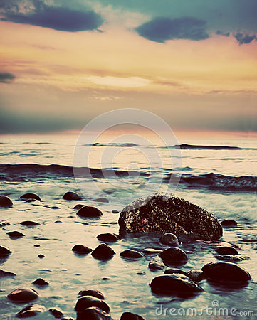 Dramatic sunrise on a rocky beach. Retro, vintage