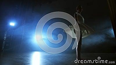 Dramatyczna scena współczesnego baletu, samotna balerina w białej sukience wykonuje kroki tańca przy użyciu nowoczesnej choreogra zbiory wideo
