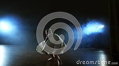 Dramatyczna scena współczesnego baletu, samotna balerina w białej sukience wykonuje kroki tańca przy użyciu nowoczesnej choreogra zbiory