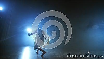 Dramatyczna scena współczesnego baletu, samotna balerina w białej sukience wykonuje kroki tańca przy użyciu nowoczesnej choreogra zdjęcie wideo