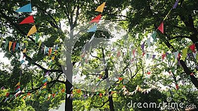 Drapeaux colorés accrochés aux branches d'arbres comme décoration festive pour la fête en plein air Soleil d'été lumineux au mili clips vidéos