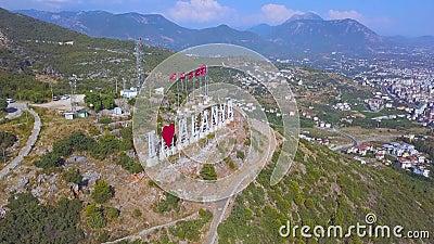 Drapeaux turcs d'affilée et inscription J'aime Alanya sur la pente d'une montagne, concept de tourisme Art Merveilleux banque de vidéos