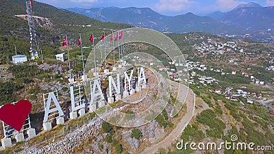 Drapeaux turcs d'affilée et inscription J'aime Alanya sur la pente d'une montagne, concept de tourisme Art Merveilleux clips vidéos