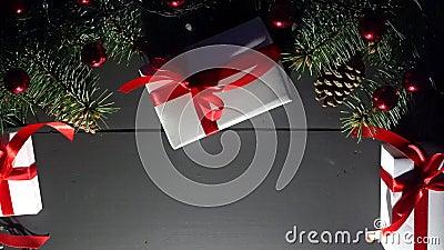 Draufsicht der obenliegenden Dekoration über schwarzen hölzernen Hintergrund mit Kiefernkegeln, Geschenken, rotem Flitter und Bli stock footage