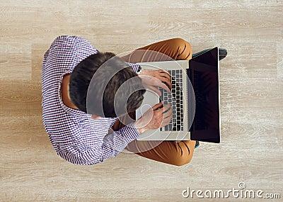 draufsicht des mannes sitzend auf dem boden und mit einem laptop arbeitend stockfoto bild. Black Bedroom Furniture Sets. Home Design Ideas