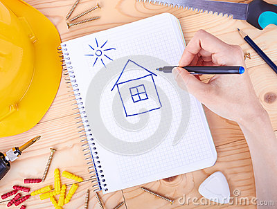 Drawing house and different tools  on a wooden background