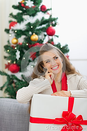 Dreaming woman holding big Christmas present box
