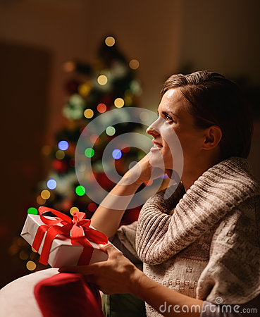 Dreaming woman sitting chair with Christmas gift