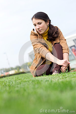 Dreamy girl sitting in a grass on a background sky and building