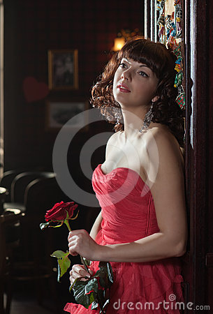Dreamy woman in red with the rose