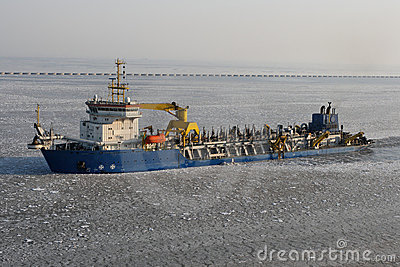Dredger ship in icy harbor