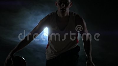 Dregla basketspelaren på domstolen med bollen i ett mörkt rum med ett panelljus i ultrarapid i röken stock video
