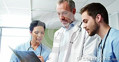 Drei Doktoren, die einen Röntgenstrahl studieren stock video footage