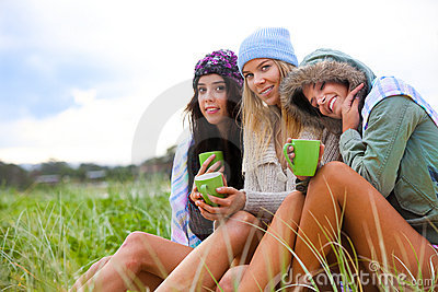 Drei Freunde rollten oben mit Kaffeetassen zusammen