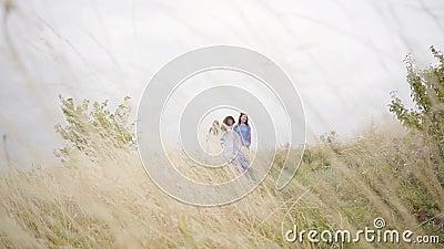 Drei Freundinnen in den schönen langen Sommerkleidern mit der Stickerei, die auf dem Gebiet gehend durch das Feld springt stock video