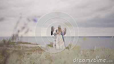 Drei Freundinnen in den schönen langen Sommerkleidern mit der Stickerei, die herum vor dem Fluss spinnt Konzept von stock video