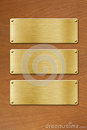Drei goldene Metallplatten über hölzernem Beschaffenheitshintergrund