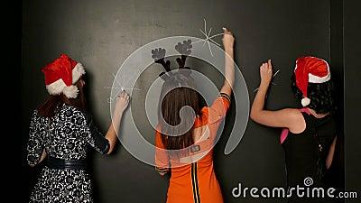Drei Mädchen zeichnen Schneeflocke auf der Wand mit Kreide stock video footage