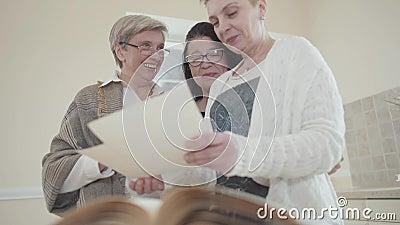 Drei positive mittlere Greisinnen, die zu Hause Ausgabenzeit mitteilen Unteres Schießen Ältere Frauenvertretung zum Freund stock video