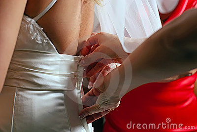 Dressing bride for wedding ceremony