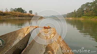 Drewniany łódkowaty dopłynięcie w rzece park narodowy Belfer drewniany łódkowaty unosić się w spokojnej rzece Chitwan park narodo zbiory