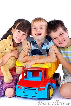 Drie jonge geitjes en hun speelgoed