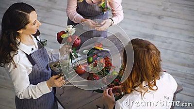 Drie jonge knappe chef-kokbloemisten werken bij de winkel van het bloemenfruit makend fruit en plantaardig boeket stock video