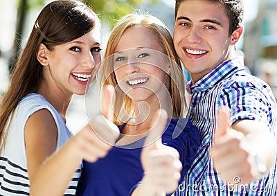 Drie jonge mensen met omhoog duimen