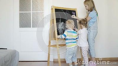 Drie kinderen trekken met kleurpotloden op een houten raad stock videobeelden