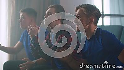 Drie mannen in blauwe t shirts Bekijk een hockeywedstrijd met vrienden die op de bank zitten en juichen en er direct op applaudis stock video