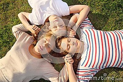 Drie meisjes houden handen en liggen op gras.