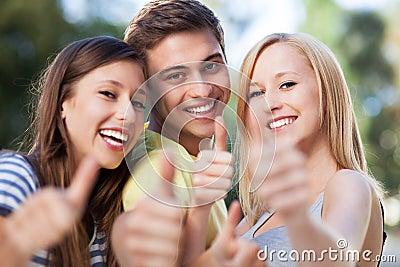Drie vrienden met omhoog duimen