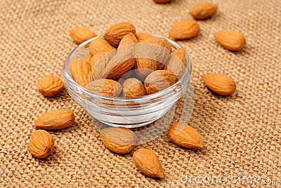 Dried almonds on glass bowl on canvas background