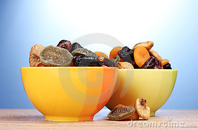 Dried fruits in bright bowls on wooden table