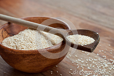 Sesame seeds on wooden spoon
