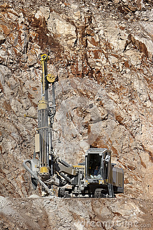 Drilling holes for demolition in a quarry