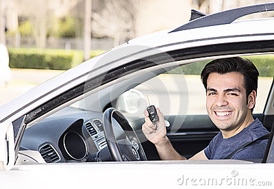 Driver in car showing keys