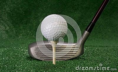 Driver che si siede davanti al collocato sul tee a su palla da golf