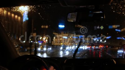 Driver drives car. In a night city in rainy weather. Night traffic jam at traffic lights stock video