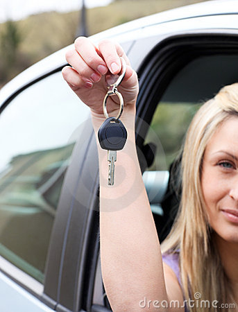 A driver holding a key after buying a new car