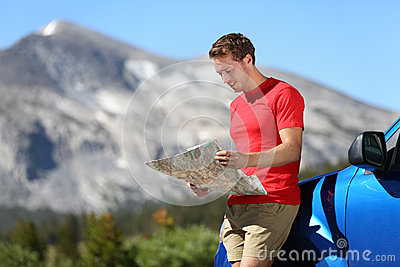 Driver man looking at map by car in Yosemite Park